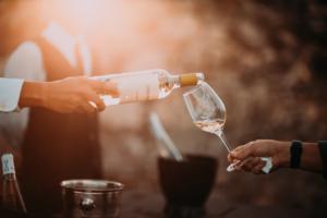 man pouring chardonnay inside a wine glass