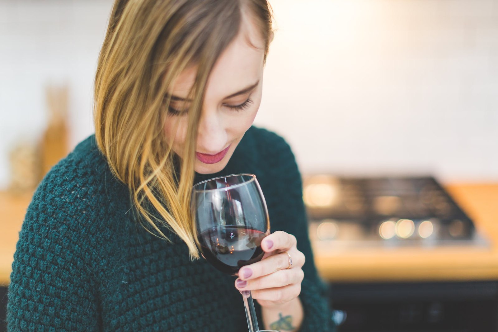 A woman smelling at her wine